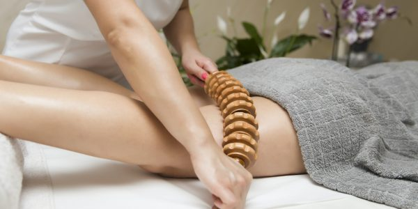 Closeup of the maderotherapy anti-cellulite massage with wooden roller massager